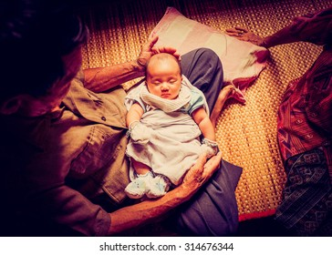 The first meeting of Asian baby infant with great-grandparents. Great grand father carrying baby placed on the lap in Asian home style atmosphere.