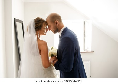 First meeting of bride and groom in hotel room. Newlyweds couple in love at wedding day. Happy marriage concept
