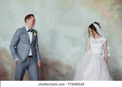 The first meeting. The groom comes into the room to the bride with a bouquet. They hug and kiss. Pink wedding dress, gray suit and stylish bouquet.