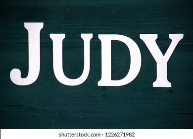 """The first name """"Judy"""" painted on a green backed board"""