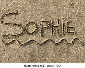 First name Sophie written in capital letter in the sand
