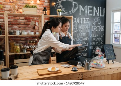 first part time job in summer concept. professional barista teaching young girl new employee how to using tablet to take customer order in cafe bar counter in coffee shop. coworkers help each other