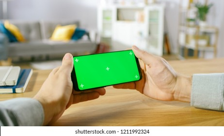First Person Close-up of the Man Holding Green Screen Smartphone in Landscape Mode and Playing Game with His Thumbs.