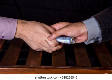 First person is giving 1000 Rupees Pakistani Currency Notes to another Person under the table .
