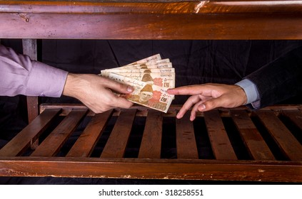 First person is giving 5000 Rupees Pakistani Currency Notes to another Person under the table .