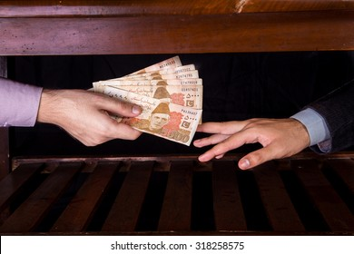 First person is giving 5000 Rupees Pakistani Currency Notes to another Person under the table .  - Shutterstock ID 318258575