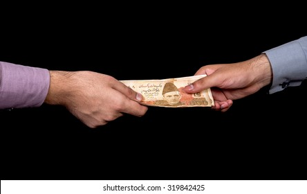 first person is giving 5000 Rupees Pakistani Currency Notes to another Person isolated with black background