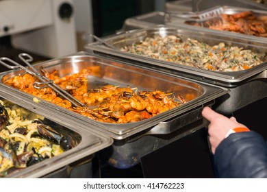 First Person Perspective of Customer Perusing Offerings at Restaurant Buffet or Food Festival, Pausing in front of Steamer Tray with Grilled Shrimp Skewers