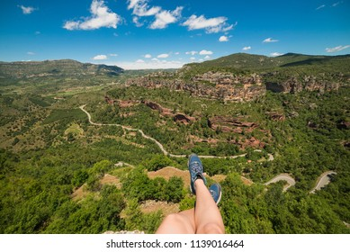 First person perspective shot from a hiker woman sitting at the edge of a cliff in Catalonia, Spain. Extreme sport hiking and traveling concept.