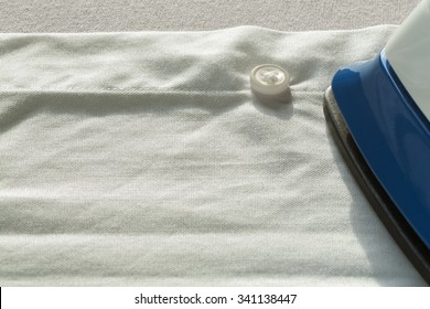 First person point of view of ironing a white shirt with low angle light sunlight.