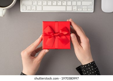 First person top view photo of female hands holding red giftbox with ribbon bow white keyboard mouse and cup of coffee on isolated grey background