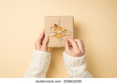 First person top view photo of female hands in white sweater unpacking craft paper giftbox with twine bow and yellow autumn leaf on isolated beige background
