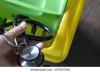First person view of Asian male doctor. He discard the black stethoscope into the plastic trash can. It means he quit medical profession or no longer want to be doctor.