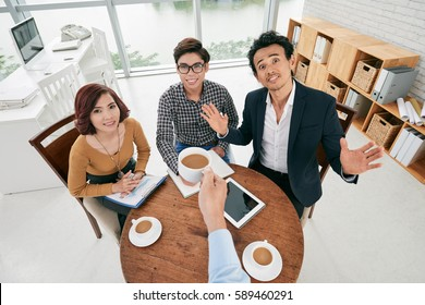 First person view of businessman cheering with cup of coffee