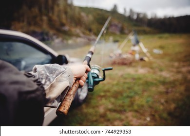 First person view, fisherman holding fishing rod for catching fish in his hand