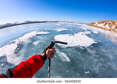 First person view gopro stick in his hand on the ice of Lake Baikal.