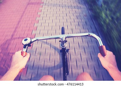 first person view of a man cycling on a city bike lane with retro filter