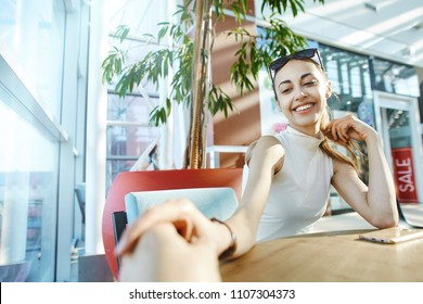 First person view of man holding hand of his smiling woman. Focus on the woman