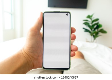 First person view of man using smartphone while lie on the bed.