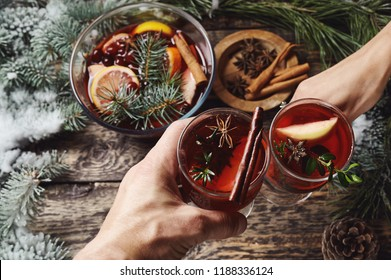 first person view of mans and womans hands holding glasses with Christmas hot mulled red wine with spices and fruits on a wooden rustic table background with spruce snow-covered branches. Traditional