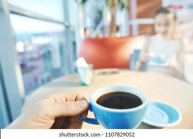 First Person View on blue Cup of coffee with woman on background. couple sitting in coffee shop and having coffee