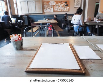 First person view of restaurant focused on the blank menu on wooden table with unidentified people in the background