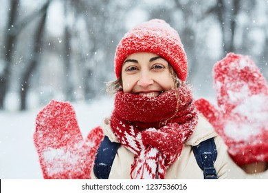 first person view of a smiling woman in warm clothes, red knitted cap, scarf and mittens walking on the snowy street under falling snowflakes after blizzard in city. Happy woman playing with the snow