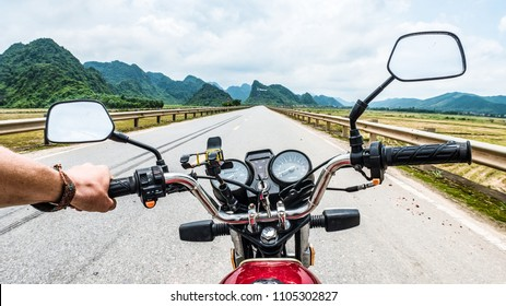 First Person View of Traveler Guy Driving Motor Bike Along Highway in Vietnam. Personal Prospective of Man with Motorcycle to Discovering and Making Adventure. Wanderlust People in Road Trip Concept.