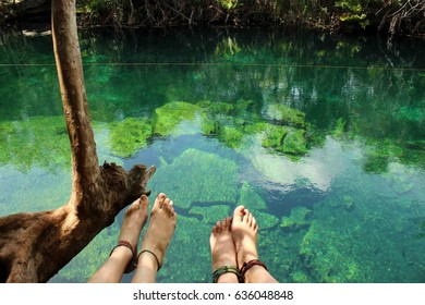 First person view of two girls feet and legs sitting at a cenote in Mexico. Tropical underground swimming caves on the Yucatan Peninsula on the Mexican Caribbean.