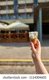 A first person view, a person walking along the road with an ice cream in his hands, shallow depth of field.