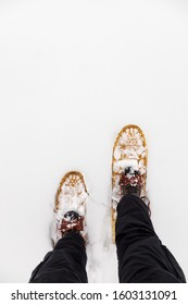 First person view of walking in snowshoes on a snowy field