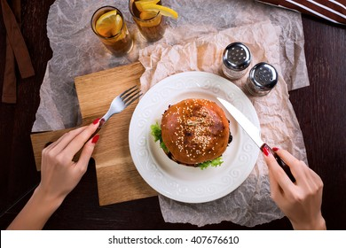 First person view of a woman preparing eat burger.