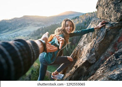 first person view of a young pretty woman hiker climbed on the cliff, looking confused and getting help