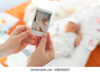 The first photo of a newborn in the hands of a female mother against a child. Instant Photo in the style of Polaroid on heavy paper.