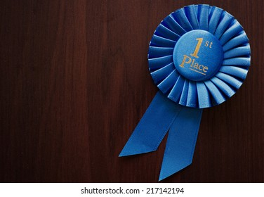 First place winners rosette or badge in pleated blue ribbon with central text to be awarded as a prize in a competition, race, or sport at an oblique angle on grey with copyspace