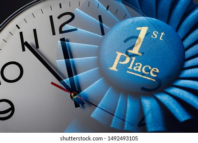 First place winners rosette over a clock dial in a conceptual composite image of winning, success, time and deadlines