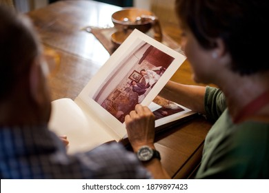 First point of view of a senior man and woman looking at a old wedding photo album. Remembering the past. Mature love. Top shot. Indoor, daytime.