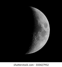 First quarter moon over dark black sky seen with a telescope from northern emisphere at night in black and white
