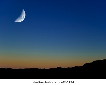 First Quarter Moon at Twilight, over clear blue sky and desert terrain.