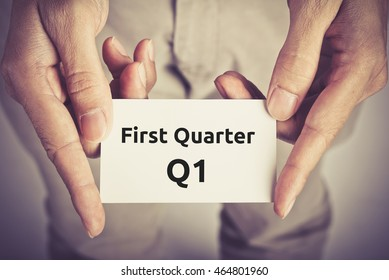 First Quarter (Q1) of business - text on card hold by man