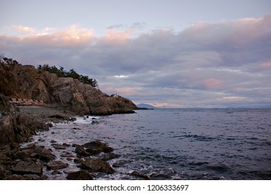 The first rays of morning sunlight hitting the rugged coastline  Pipers Lagoon Park Vancouver Island rock cliffs are dominating scenery along the rugged beach ocean background colorful cloudy skies