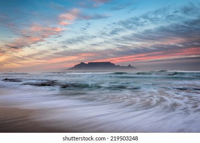 The first rays of sunlight tinge clouds with red colours above the world famous Table Mountain in the Cape.