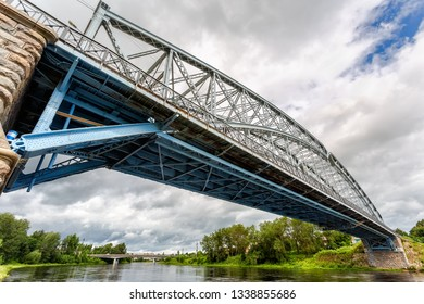 First in Russia steel arch bridge across Msta river in summer day. Was built in 1905. Borovichi, Russia