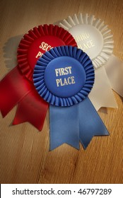 First, second, third place ribbons shot on dramatically lit rough-hewn wood