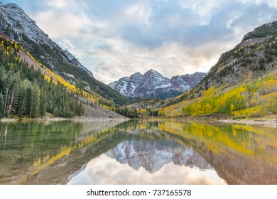 First snow and autumn colors adorn the Maroon Bells, reflected in Maroon Lake, part of the Elk Mountain range, in the White River National Forest, near Aspen, Colorado.