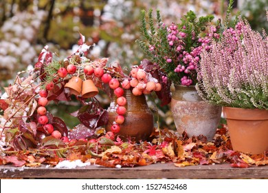 First snow in the garden, heather, snowberries, apple wreath  with ceramic mini pots, snowberries in clay vase, girl's grape on fading leaves on bush background, vintage style, daylight