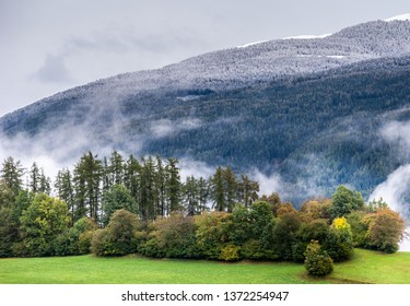 First snow in the mountains. Snow capped mountains and green pasture lands. Change of weather. Dolomites, Sudtirol, Italy