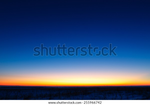 The first stars in the background of a bright sunset.
