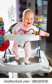 First steps in the baby walker by little baby girl