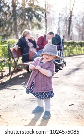 The first steps of the child in the big world. Young happy family with cheerful child having fun in park on sunny day.